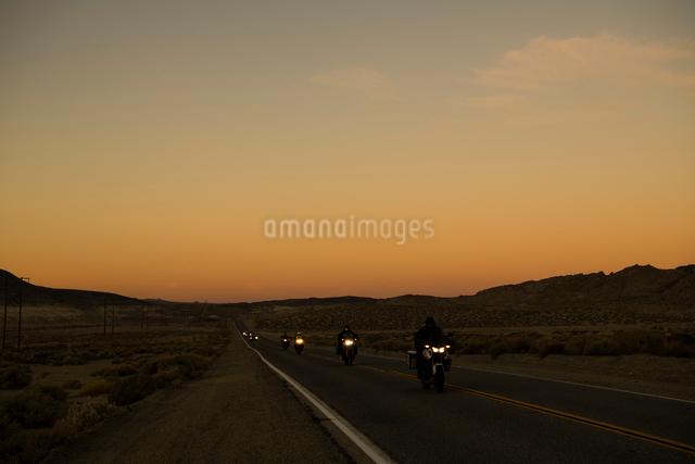 朝焼けの道を走るバイクの列の写真素材 [FYI01504489]
