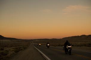 朝焼けの道を走るバイクの列の写真素材 [FYI01504593]