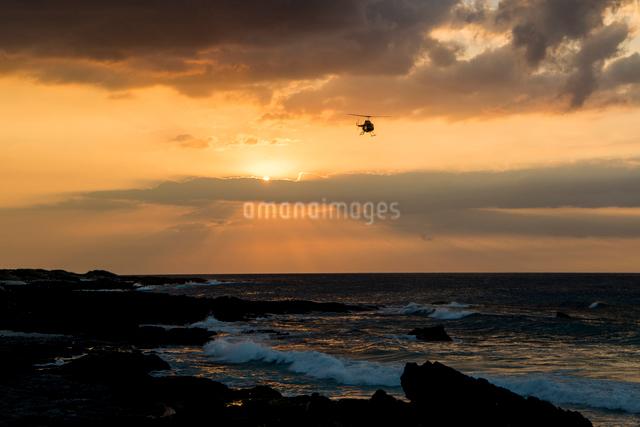 夕暮れの海を飛ぶヘリコプターの写真素材 [FYI01504915]