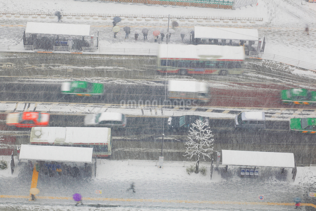 吹雪の中野駅前北のバスターミナルと道路の写真素材 [FYI01508959]