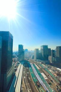 東京駅と電車と丸の内の都心のビル群と太陽の光芒の写真素材 [FYI01509038]