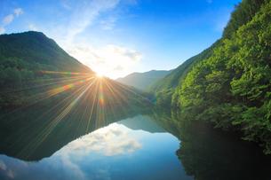水鏡の新緑の竜ヶ沢ダムと夕日の光芒の写真素材 [FYI01509585]