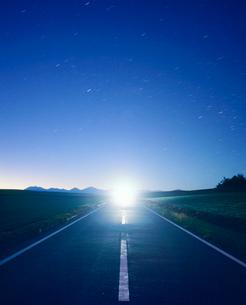 黎明の道路と十勝連峰とヘッドライトの光芒の写真素材 [FYI01509875]