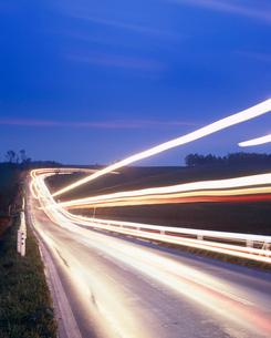 黎明の道路とヘッドライトの光跡の写真素材 [FYI01510582]
