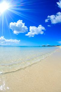 奥間ビーチの渚に打ち寄せる波と太陽の光芒の写真素材 [FYI01510660]