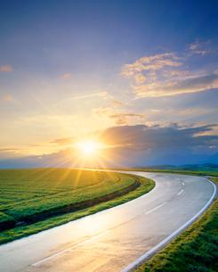雨上がりの道路と朝日と小麦畑の写真素材 [FYI01511464]