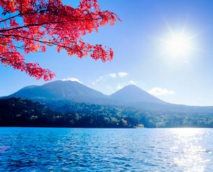 紅葉のナナカマドとオンネトーと雌阿寒岳と阿寒富士と太陽の写真素材 [FYI01511869]