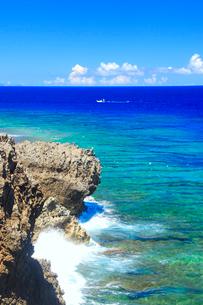 辺戸岬の岩礁とパドルサーフィンと漁船と波しぶきの写真素材 [FYI01512049]