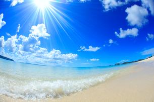 奥間ビーチの渚に打ち寄せる波と太陽の光芒の写真素材 [FYI01512141]
