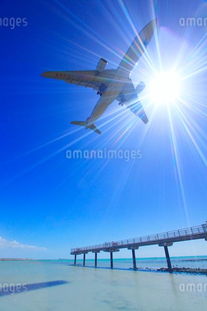 香港航空の航空機と太陽の光芒と誘導灯の桟橋と南方向の海の写真素材 [FYI01512571]