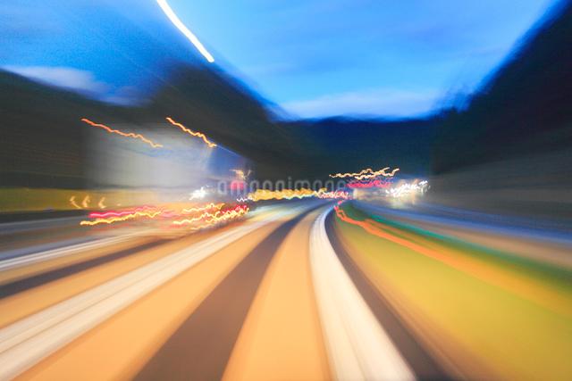 薄暮の中国自動車道の下りカーブ注意レーンの走行とトラックの写真素材 [FYI01513290]