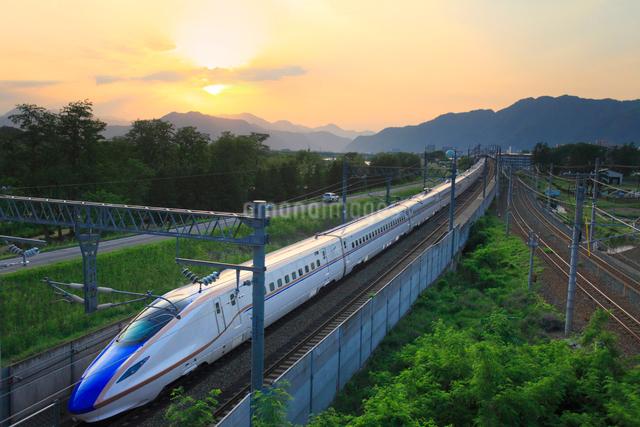 北陸新幹線E7系と夕日の写真素材 [FYI01513422]