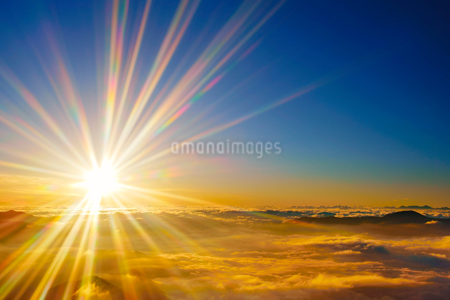 八ケ岳などの山並みと雲海と朝日の光芒の写真素材 [FYI01514572]
