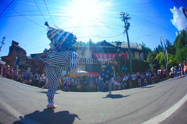 岳の幟の獅子舞と別所温泉の街並みと太陽の光芒の写真素材 [FYI01515357]