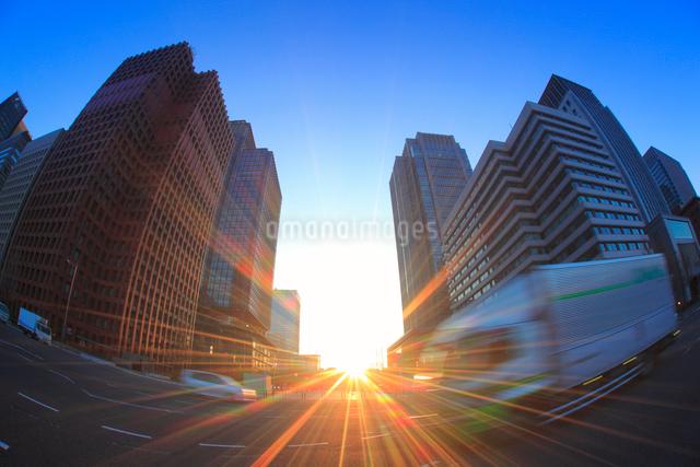丸ノ内のビル群と行き交う自動車と朝日の写真素材 [FYI01515532]