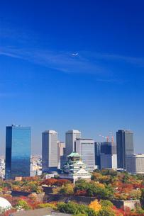 紅葉の大阪城と大阪ビジネスパークのビル群と飛行機の写真素材 [FYI01515688]