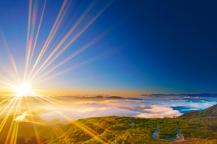 甲斐駒ケ岳などの山並みと雲海と朝日の光芒と乗鞍エコーラインの写真素材 [FYI01516043]
