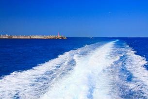 泊港の赤灯台と航跡とクルーザーと飛行機の写真素材 [FYI01516697]