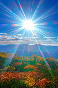 乗鞍岳位ヶ原の紅葉と八ケ岳方向の山並みと太陽の光芒の写真素材 [FYI01516775]