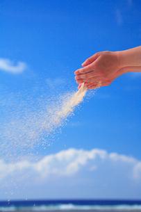 手からこぼれ風に舞う砂と海の写真素材 [FYI01521728]