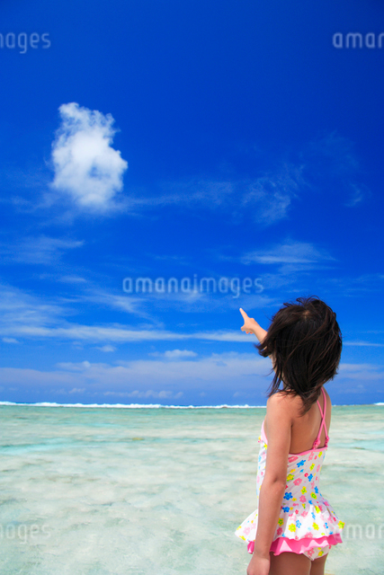 雲を指差す水着の女の子と海の写真素材 [FYI01522234]