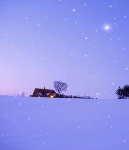 雪の降る雪原と民家 夕景の写真素材 [FYI01522449]