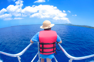 船首に立つ麦わら帽子の男の子と海の写真素材 [FYI01522778]