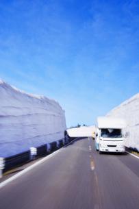 残雪の壁と道路走行とキャンピングカーの写真素材 [FYI01522802]