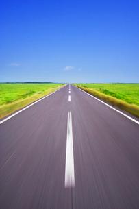 牧草地と道路走行の写真素材 [FYI01522931]
