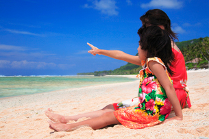 ビーチに座って遠くを指差す娘と母親の写真素材 [FYI01523315]