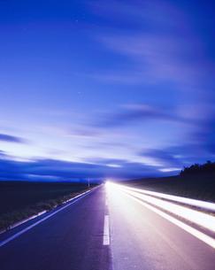 ヘッドライトの光跡と朝の流れる雲の写真素材 [FYI01524450]