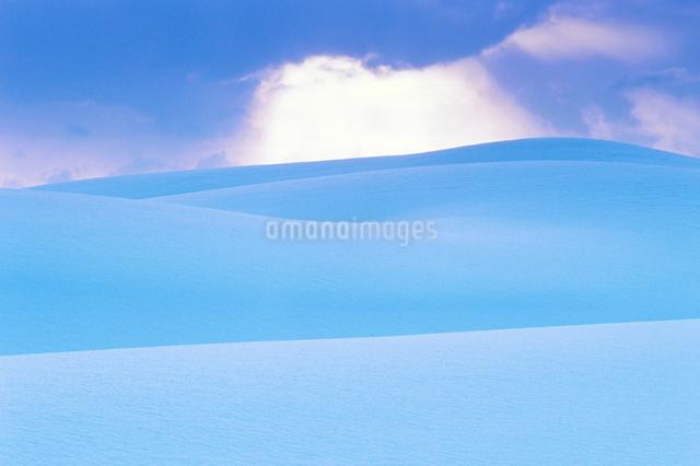 雪原と雲間の光夕景の写真素材 [FYI01525136]
