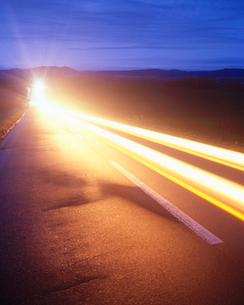 朝の道路とヘッドライトの光跡の写真素材 [FYI01525521]
