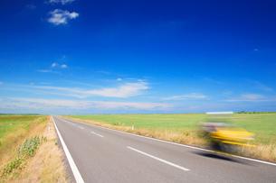 道路を走るバイクと牧草地の写真素材 [FYI01526179]