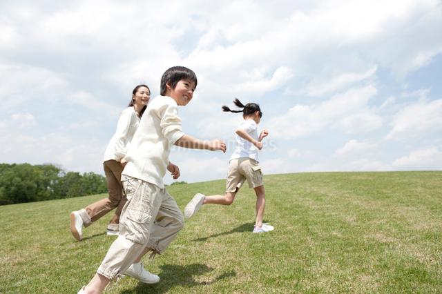公園を走る母と子供3人親子の写真素材 [FYI01527842]