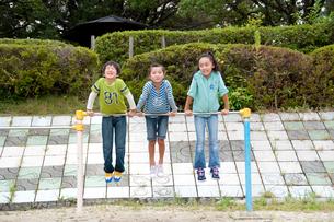 公園の鉄棒で遊ぶ子供男女3人の写真素材 [FYI01527940]