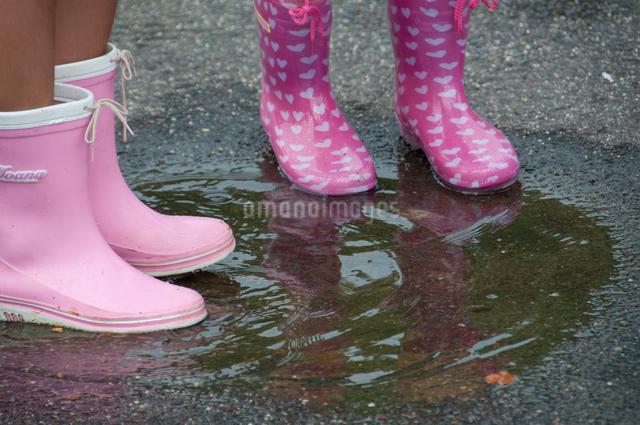 雨天の水溜りで長靴を履いて遊ぶ女の子の足の写真素材 [FYI01527967]