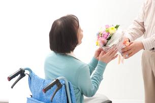 車椅子の老人女性に花束を渡す老人男性の写真素材 [FYI01528136]