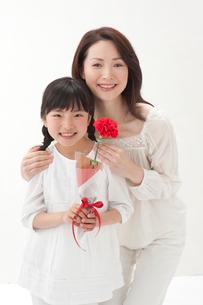 赤いカーネーションを持つ女の子と母の写真素材 [FYI01528148]