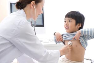 男の子の患者を聴診器で診察する女医の写真素材 [FYI01528394]
