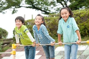 公園で鉄棒をする子供男女3人の写真素材 [FYI01528478]
