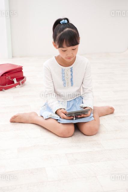 ゲーム機で遊ぶ女の子の写真素材 [FYI01528631]