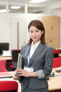 オフィスでIDカードを首にかけてファイルを持つ20代OLの写真素材 [FYI01528716]