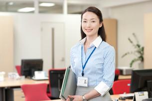 オフィスの中で立つIDカードを首にかけてファイルを持つOLの写真素材 [FYI01528818]