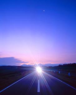 朝の道路とヘッドライトと十勝連峰の写真素材 [FYI01528821]