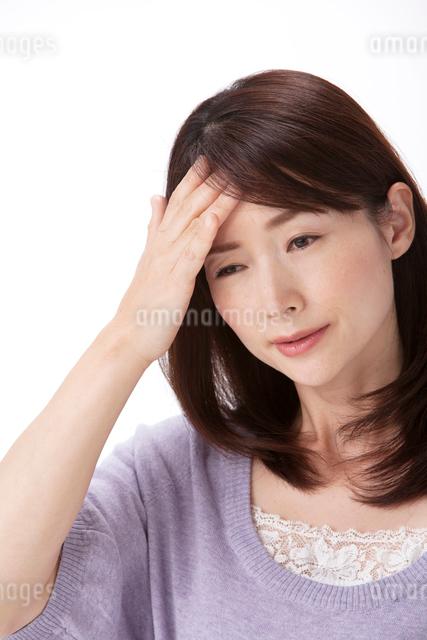 発熱で頭に手をやる女性の写真素材 [FYI01529039]
