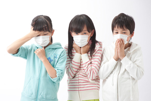 マスクをして風邪の症状の子供男女3人の写真素材 [FYI01529258]