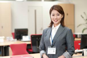 オフィスの中で立つIDカードを首にかた20代OLの写真素材 [FYI01529333]