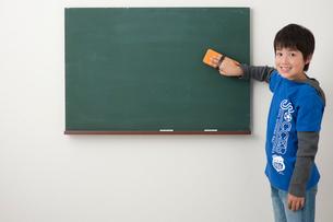 黒板の前で黒板消しを持つ男の子の写真素材 [FYI01529352]