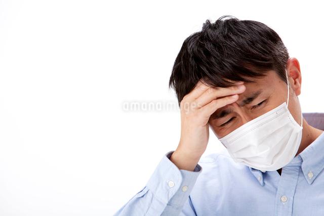 発熱で頭に手をやるマスクをした男性の写真素材 [FYI01529385]